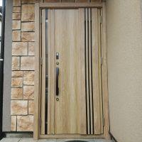 デザインされた石材の壁にバランスがいい木目調のドア【LIXILリシェントM83型】
