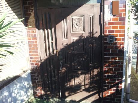 (施工前)木製のドアです。 塗装が色あせて、ドアが閉まりにくくなっています。